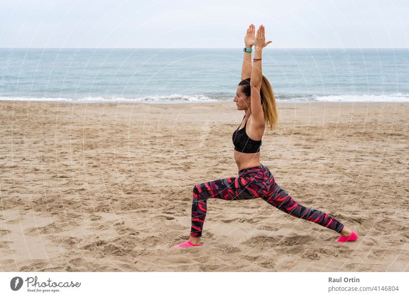 Young fit attractive female practicing yoga warrior one pose , Virabhadrasana posture.Athletic woman working out outdoors, at the beach seaside , lifestyle fitness training concept.
