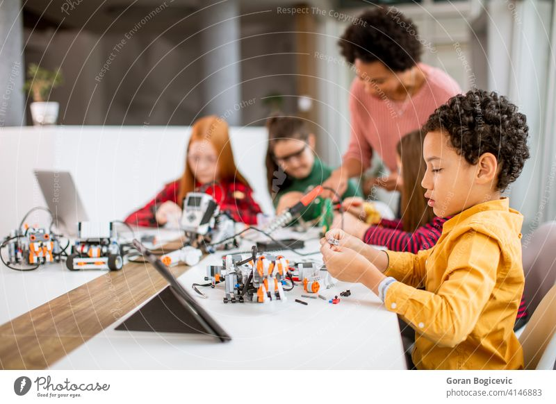 Happy kids with their African American female science teacher with laptop programming electric toys and robots at robotics classroom education technology