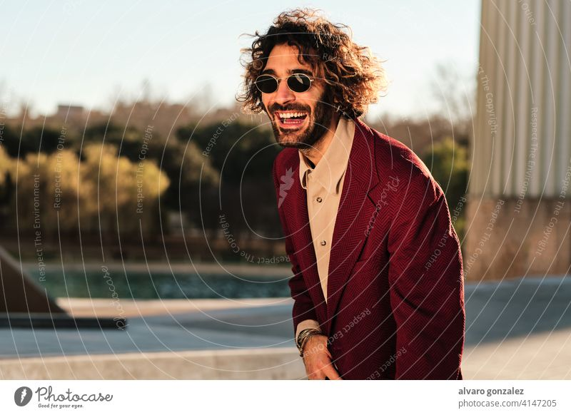 Confident man smiling while standing outdoors. portrait hipster urban street clothes stylish city trendy clothing confidence style coat sombrero one confident