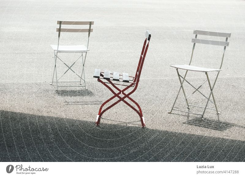 2x Snow White and 1x Rose Red: three folding chairs with their shadows are standing in the sun, two of them white and one red. Chair Folding chair Spring Bright