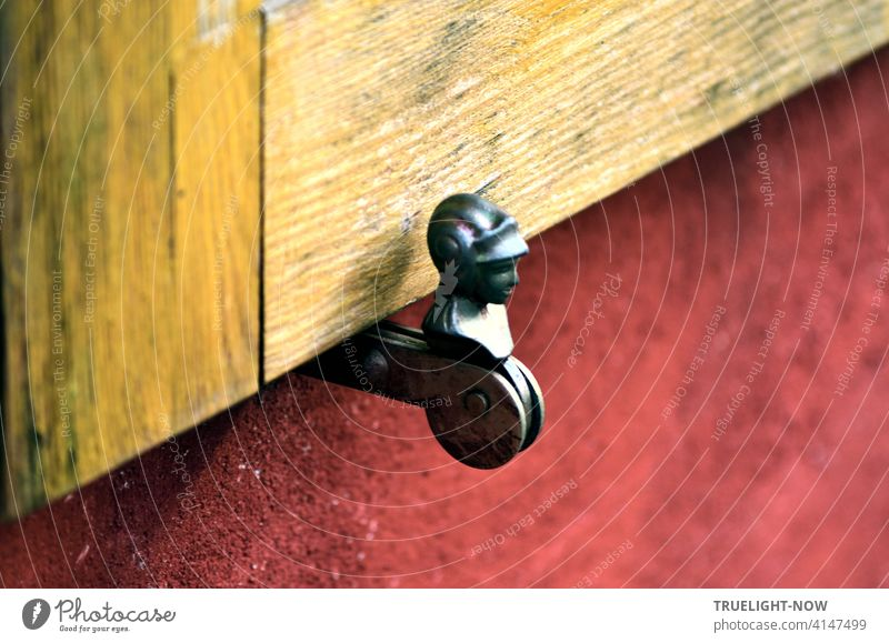 Shutter holder made of iron and steel, embedded in a red house wall, in front of a natural wood shutter running diagonally through the picture, Shop retainer