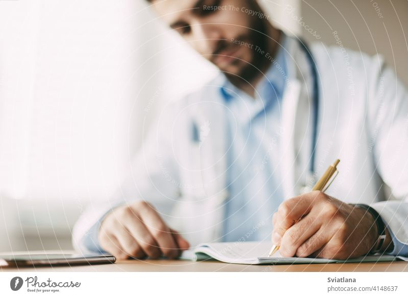 Friendly young male doctor of oriental appearance sits at a desk in his office and takes notes in a notebook, close-up medicine person health clinic stethoscope