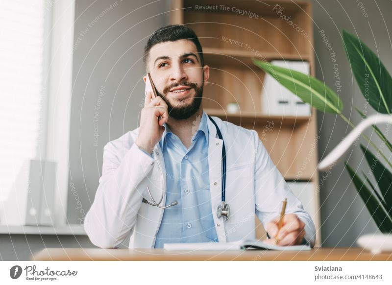 A young doctor of oriental appearance is talking on the phone, sitting at the table and making notes in a notebook medicine man health medical professional