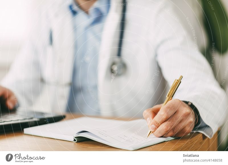 A young doctor of oriental appearance works while sitting at the table in the network with a laptop and makes notes in a notebook medicine person health clinic
