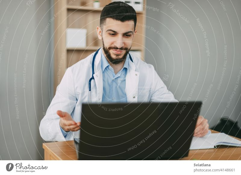 Young male doctor conducting online video consultation on laptop in his office patient health clinic stethoscope therapist online counseling diagnostics