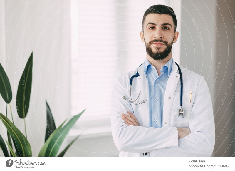 Smiling young doctor with stethoscopes and white medical gown stands in his office with arms crossed medicine man health professional cheerful male healthcare