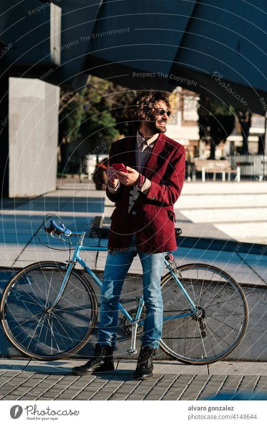Hipster man using his mobile phone outdoors. hipster bicycle smartphone urban city lifestyle wireless connection communication stylish trendy gadget