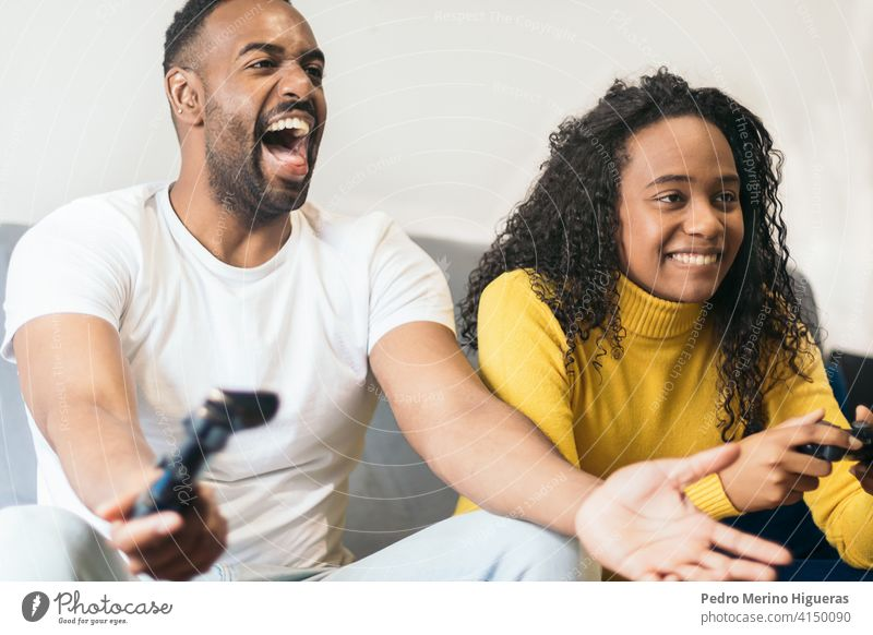 black couple playing video game with enthusiasm at home. female console fun people happy gamer gaming man sitting young entertainment woman sofa relationship