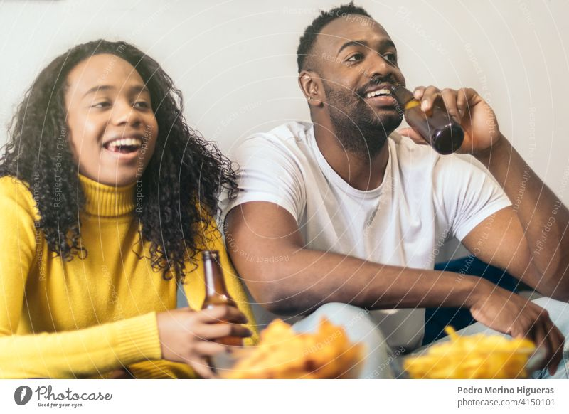 afro-american couple smiling and drinking beer at home happy african friends girlfriend boyfriend young together woman black alcohol fun leisure joy beverage