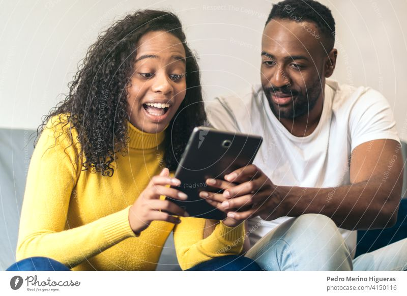 afro american couple watching tablet at home man woman internet black people happy technology smiling young online movie lifestyle african american female adult