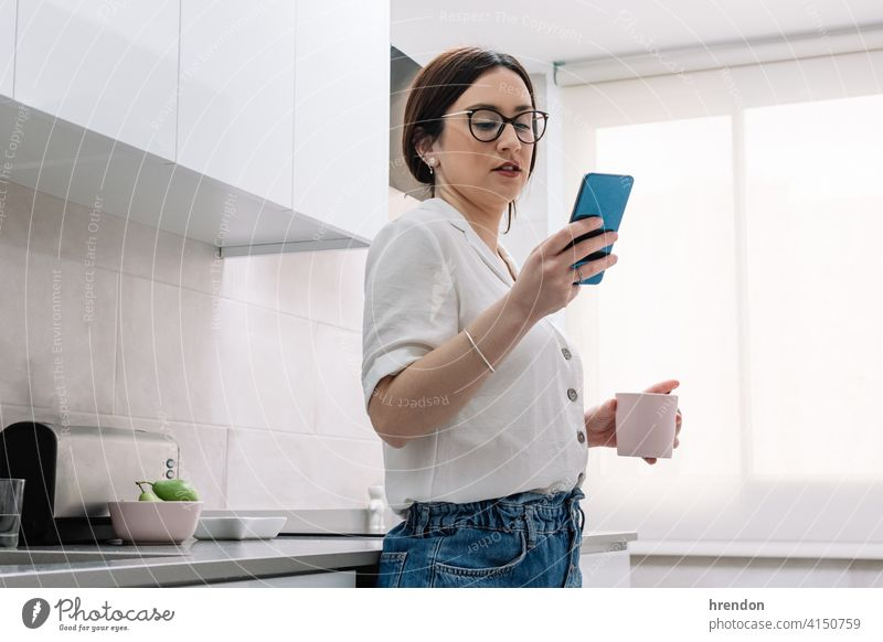 woman drinking coffee in the kitchen while using her smartphone indoor one person relaxation young adult apartment comfortable routine relaxing cozy brunette