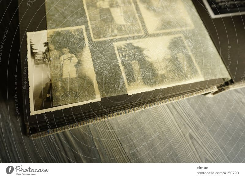 View into an old photo album with black and white photographs and parchment paper between the black pages / analog photography / dementia therapy Photo album