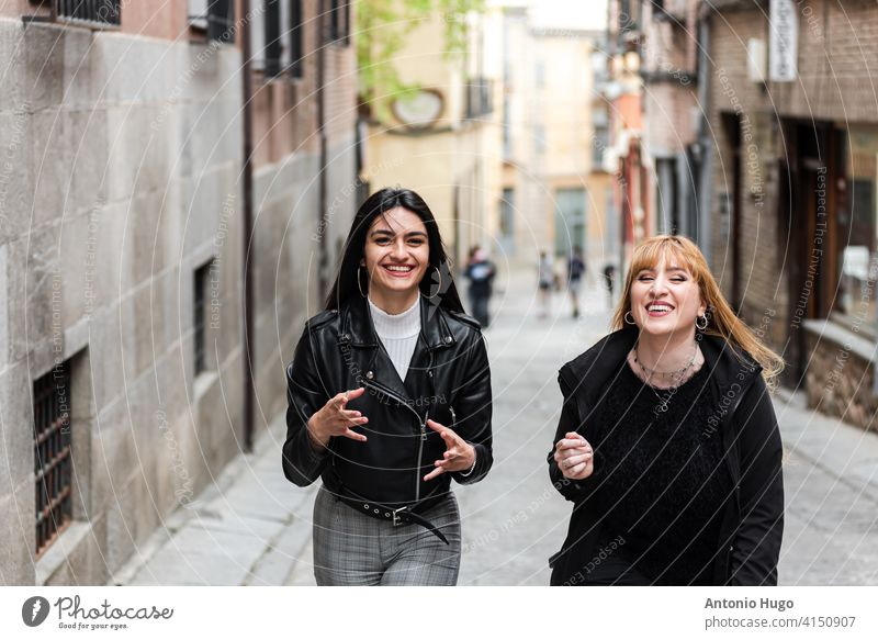 Two women sightseeing and laughing around the old city. brunette blonde 2 woman walking tourist historical vacation friendship female fun togetherness