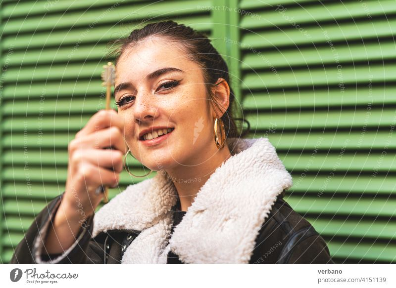 happy young woman holding a key with her hand owner new white business female sale people property house background buy rental loan investment apartment agent