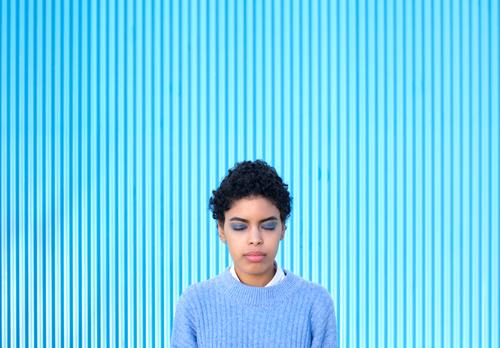Young African American girl with her eyes closed on a blue background. grateful latin happy adult african afro american attack latina closed eyes attractive