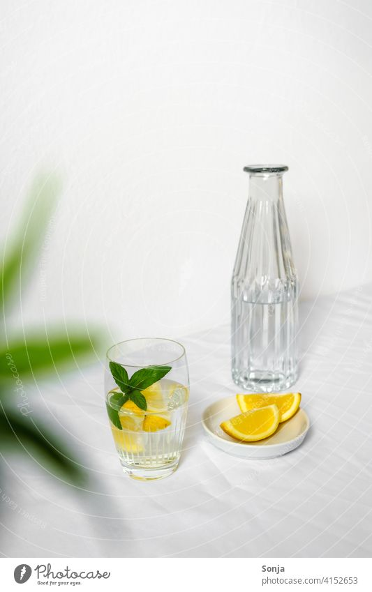 A water bottle and a drinking glass with water, lemon and peppermint on a white tablecloth Water Lemon Peppermint Cold drink Refreshment Fresh Lemonade Yellow