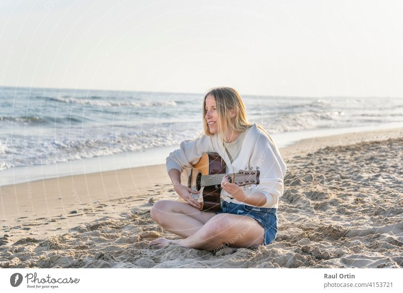 Young caucasian woman playing acoustic guitar on sandy beach.travel lifestyle, summer vacation background with copy space. Woman Guitar Playing Beach Summer