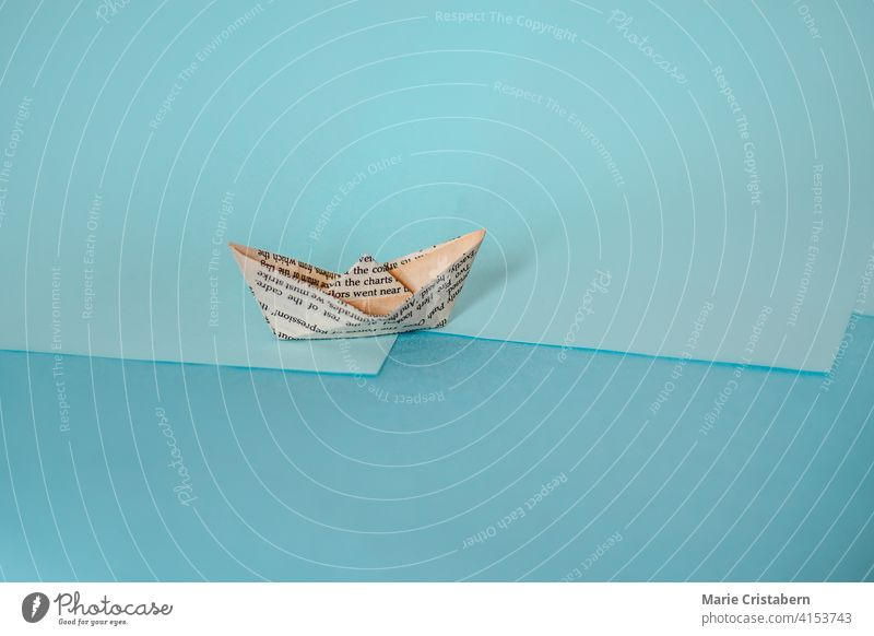 Conceptual photo of a paper boat made from old newspaper, showing concept of economy and finance sparse copy space day indoors no people creative idea transport