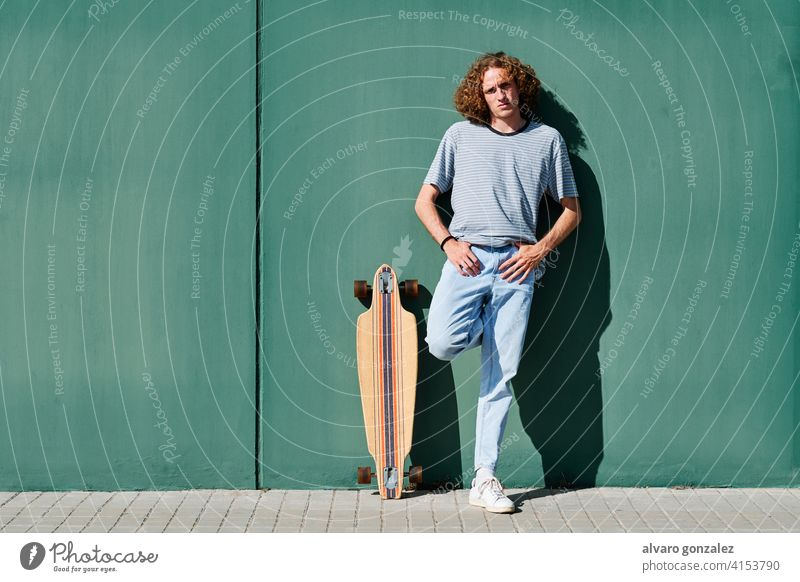 a young man with curly hair standing on a green wall on a sunny day with his skate or longboard che skateboard attractive person skateboarding sport skater male