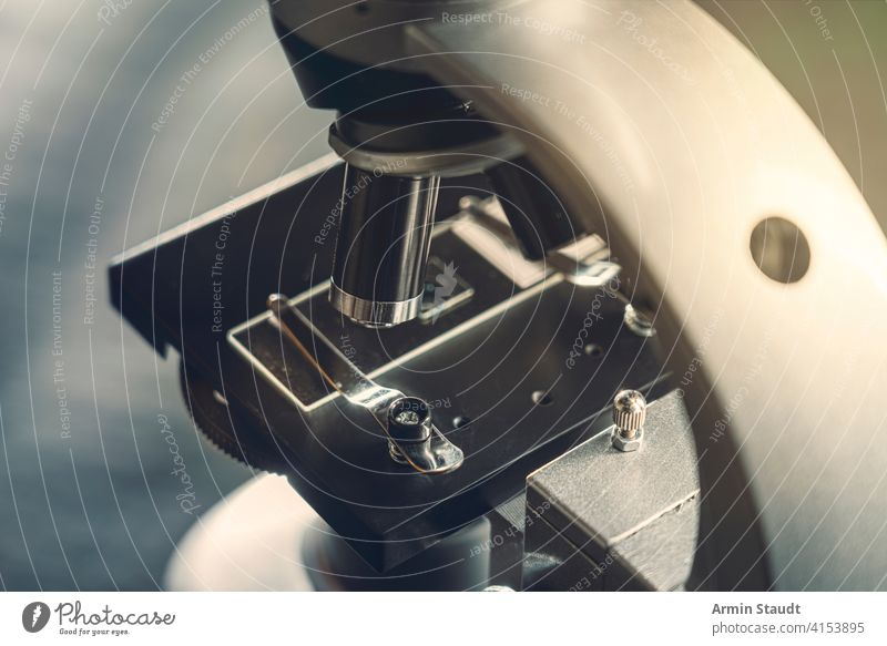 details of a silver microscope, with black background analyzing biology biotechnology brightly lit chemistry close-up closeup discovery education equipment
