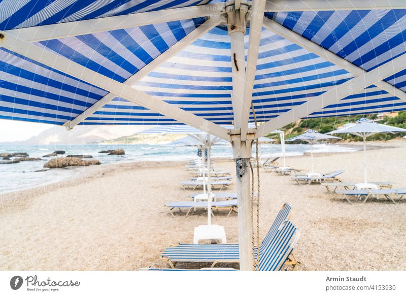 deckchairs and parasols at an empty beach background bay blue cloudscape coast coastline holiday journey landscape leisure mountain nature nobody ocean outdoor