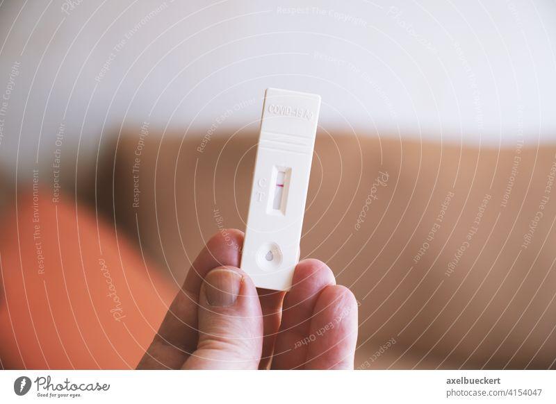 hand holding corona covid-19 rapid antigen self test showing negativ result negative home person testing coronavirus self-test kit using diagnostic health care