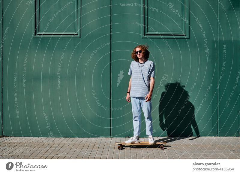 a young man with curly hair skating outdoors with a green wall behind him longboard che skateboard attractive person skateboarding sport skater male guy casual