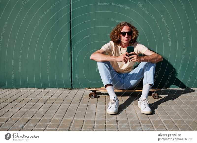 a young man using his smartphone and seated on his skateboard or longboard with a wall behind him che attractive person skateboarding sport skater male guy