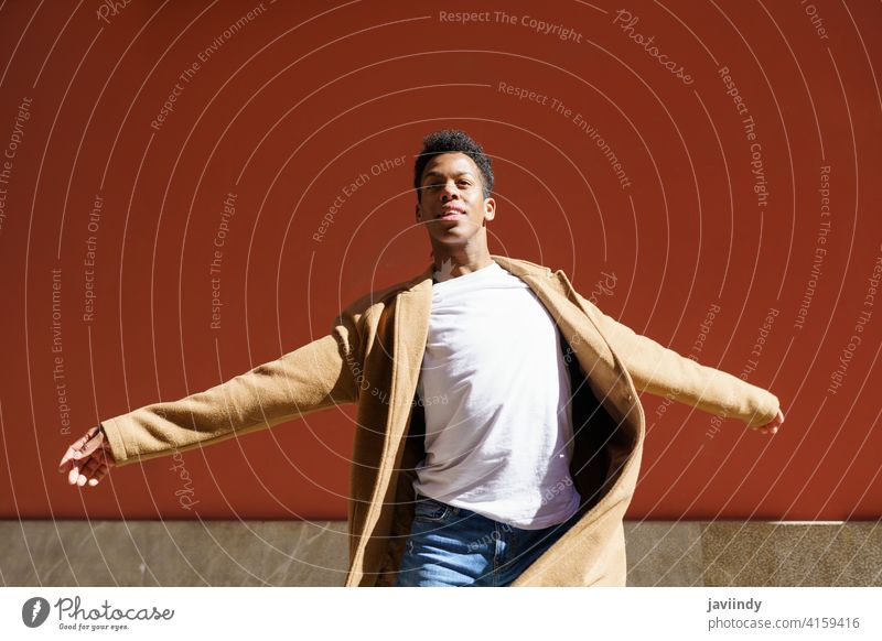 Young Cuban man dancing on red urban wall. black street happiness male cuban young expression person happy looking dancer outdoor one joy casual lifestyle adult