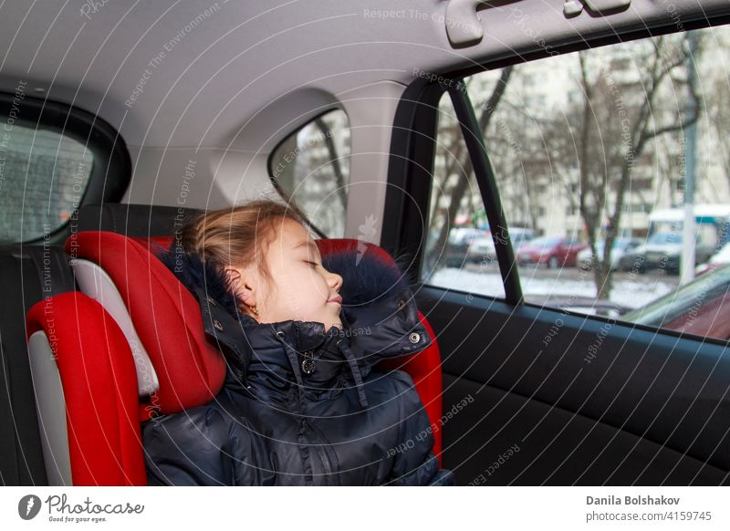 girl in blue warm clothes sits unbuckled in a car seat and sleeps daughter comfortable back door red window safely defence secure passenger inside hat vehicle