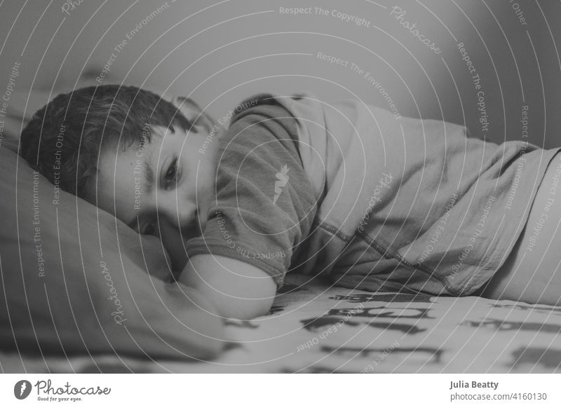 Tired young boy waking up from a nap; bear print flannel sheets rest napping child bed bedroom interior home pillow house comfortable relax pillows sleep