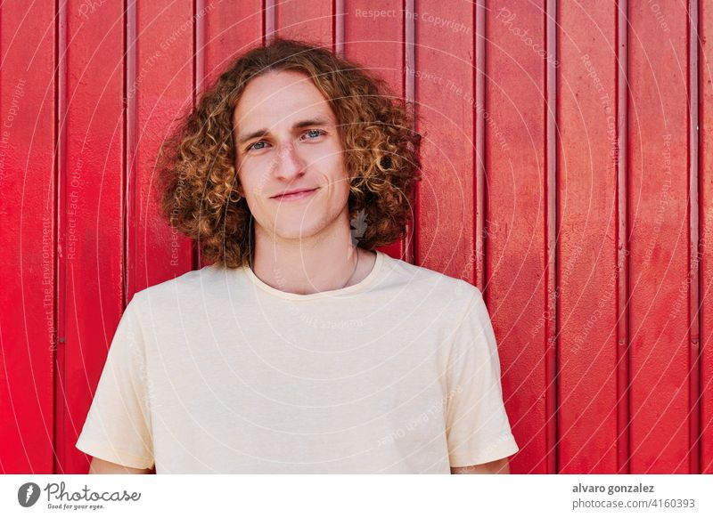 a young man with curly hair and green eyes smiling and looking at camera che attractive person male guy casual white handsome one isolated portrait adult