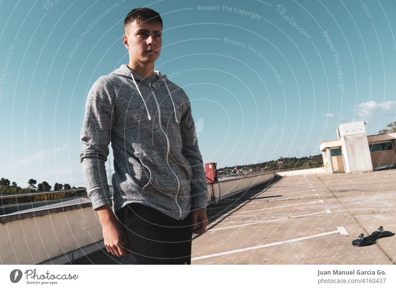 A teenager with short hair takes a break from skateboarding in an abandoned parking lot sweatshirt layered haircut alone rooftop seriousness clear sky shorts