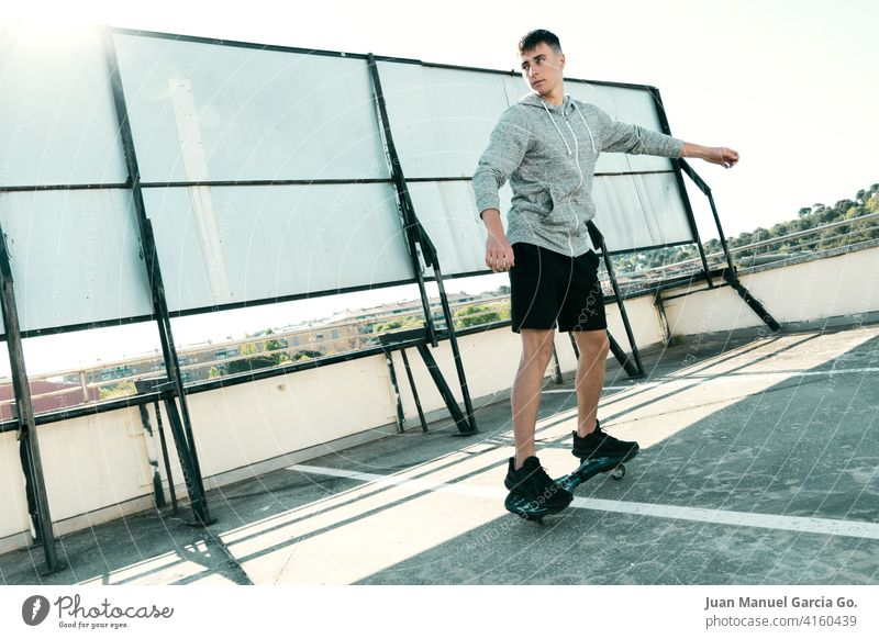 Rider on waveboard plays in abandoned parking lot teenager sweatshirt layered haircut alone rooftop seriousness clear sky shorts sport young leisure game