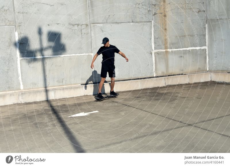 Teenager dressed in black and cap skateboarding in industrial zone teenager parking lot abandoned layered haircut solo rooftop seriousness clear sky shorts