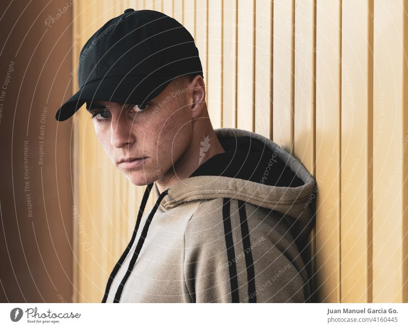 Teenager with cap in foreground looks at camera teenager black sweatshirt khaki serious intense puberty pimples acne bald door industrial zone tracksuit