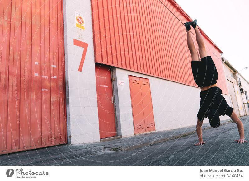 Young man with cap and black clothes does a handstand faced industrial building with the number seven Handstand balance adolescent Acrobatic young local red