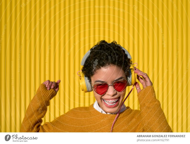 Gorgeous young afro latina girl with headphones having fun dancing on a sunny day people woman music portrait adult urban love african american attractive