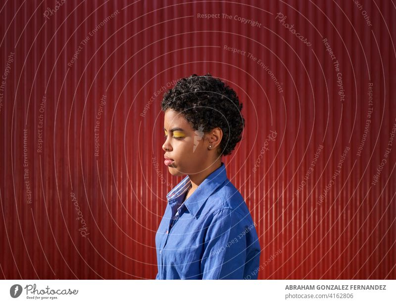 Side view of an adult black female posing on a red background with her eyes closed. portrait woman fashion studio afro latin cute young pretty african