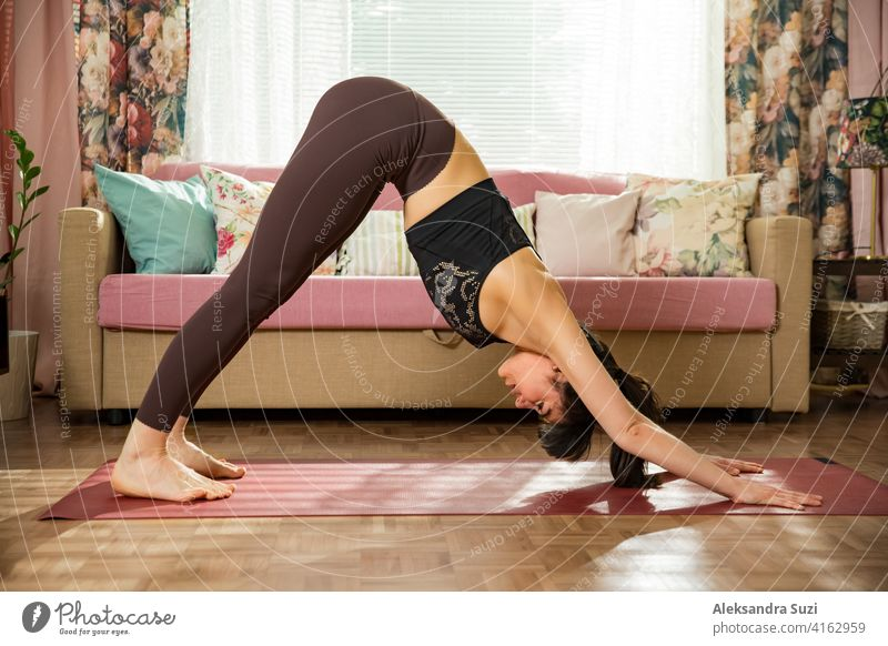 Young beautiful woman practicing yoga at home. Stylish cozy home interior. Doing yoga exercises and enjoying early morning. Healthy lifestyle active activity