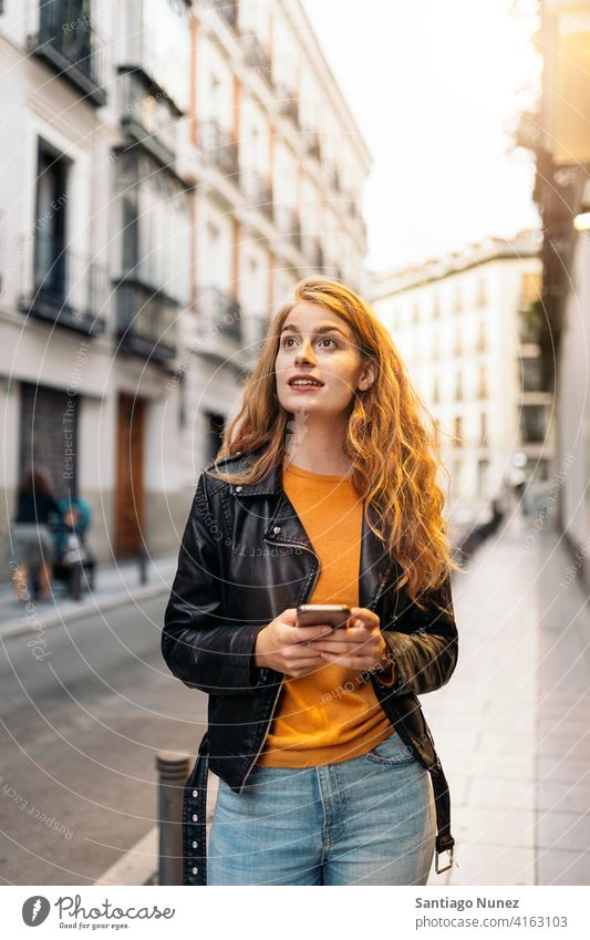 Ginger Head Woman Portrait portrait girl woman using phone ginger head pretty young street city front view outside typing cellphone looking smartphone