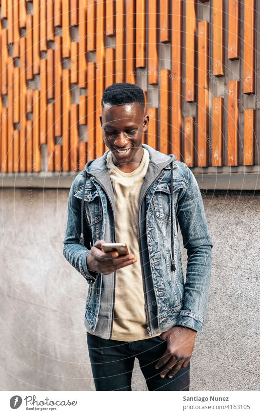 Portrait Of Young African American Man portrait african american using phone street typing mobile phone front view looking phone black ethnic afro cellphone