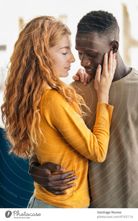 Loving Multiethnic Couple Portrait looking at each other kissing portrait front view standing relationship multi-racial black man caucasian multi-cultural