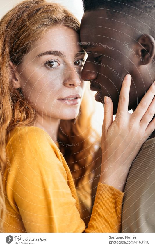 Loving Multiethnic Couple Closeup closeup looking at each other kissing portrait front view standing relationship multi-racial black man caucasian