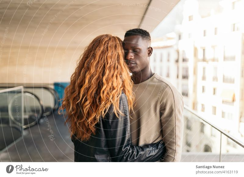 Loving Multiethnic Couple Portrait looking at each other portrait front view hugging standing relationship multi-racial black man caucasian multi-cultural