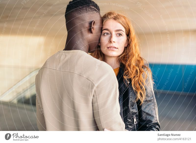 Loving Multiethnic Couple Hugging looking at each other portrait front view hugging standing relationship multi-racial black man caucasian multi-cultural