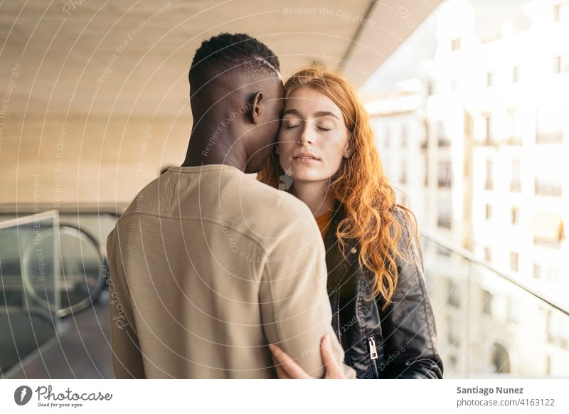 Loving Multiethnic Couple Hugging eyes closed portrait front view hugging standing relationship multi-racial black man caucasian multi-cultural multi-ethnic