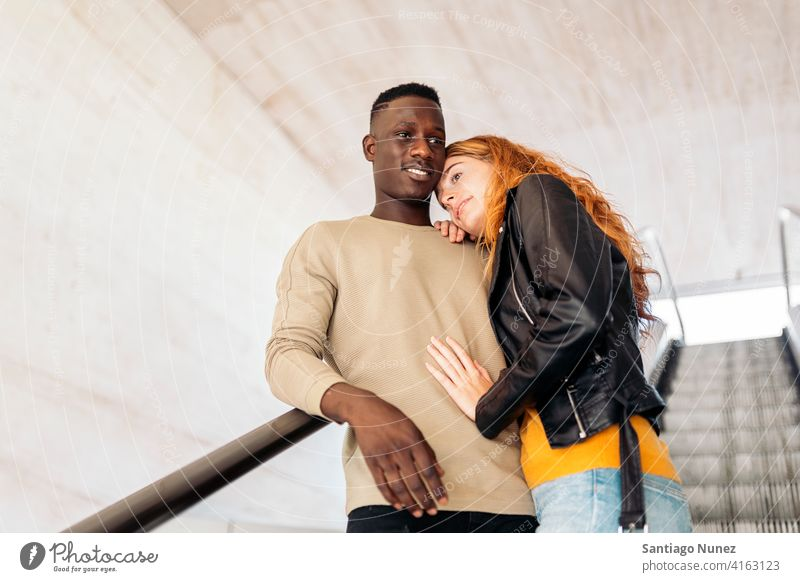 Loving Multiethnic Couple Portrait stairs smiling hugging looking at each other portrait front view standing relationship multi-racial black man caucasian