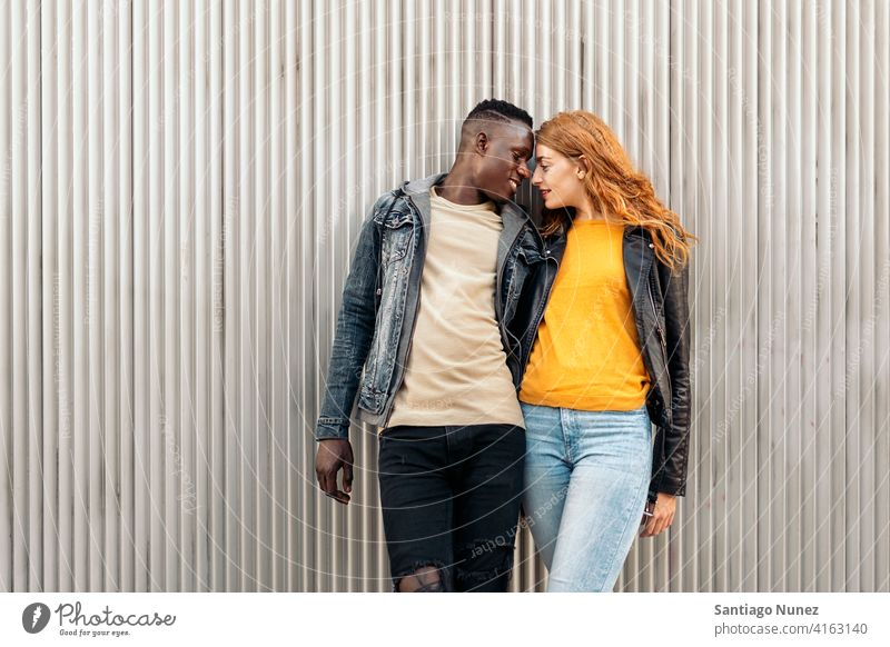 Loving Multiethnic Couple looking at each other kissing portrait front view standing relationship multi-racial black man caucasian multi-cultural multi-ethnic