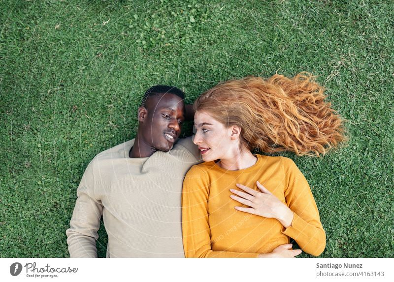 Multiethnic Couple Cuddling in the Grass lying grass looking at each other top view portrait relationship multi-racial black man caucasian multi-cultural